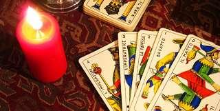 immagine raffigurante una candela accesa e 5 carte da briscola