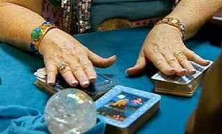 immagine raffigurante un mazzo di tarocchi tagliato in 3 parti con le mani della cartomante sopra di essi